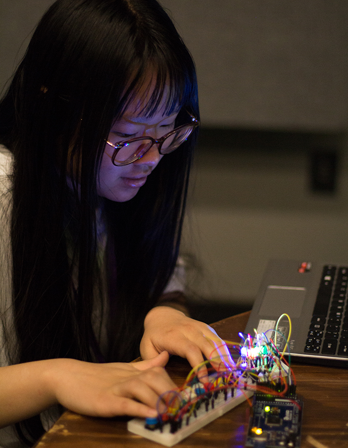 A single T9Hacks participant using their hands to test a physical computing project they built.